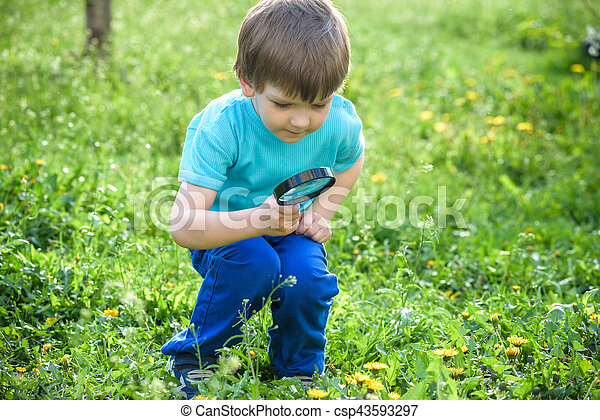 Young boy exploring nature in a meadow with magnifying glass - csp43593297