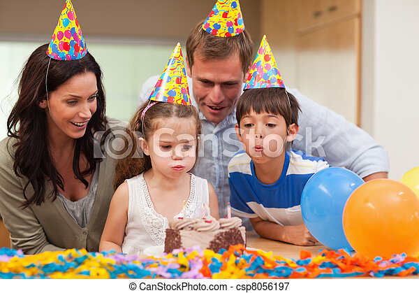Young boy helping his little sister to blow out the candles on her birthday cake - csp8056197