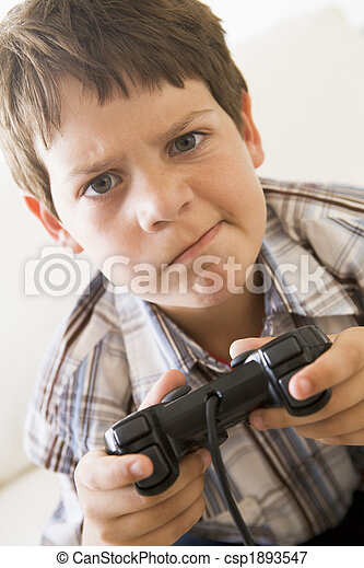 Young boy holding video game controller looking confused - csp1893547
