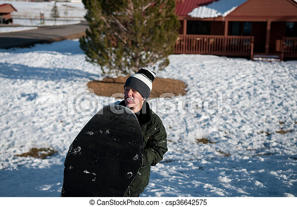 7c97ee93f Young boy in the snow holding sled.