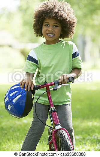 Young Boy Learning To Ride Bike In Park - csp33680388
