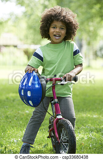 Young Boy Learning To Ride Bike In Park - csp33680438