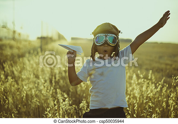 Young Boy playing to be airplane pilot, funny guy with aviator cap and glasses, carries in his hand a plane made of paper - csp50035944