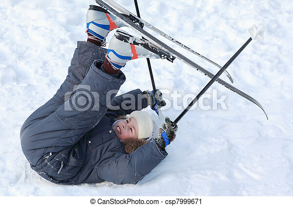 Young boy with cross-country skis and poles lying on snow and put up feet on pure white snow - csp7999671