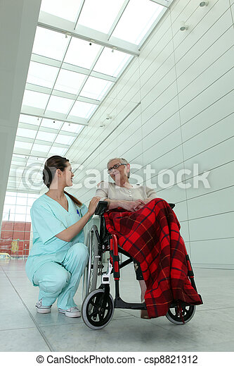 young brunette nurse and elderly dame in wheel chair in hospital - csp8821312