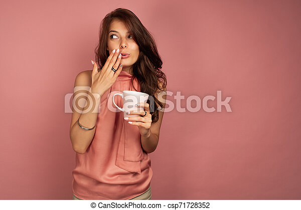 Young brunette wants to tell a secret while drinking tea or coffee - csp71728352