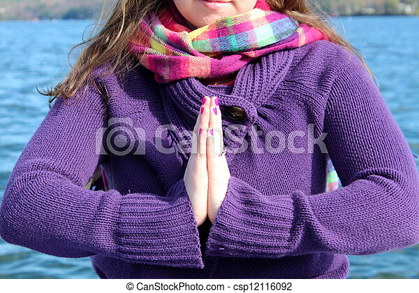 Young brunette with praying hands - csp12116092
