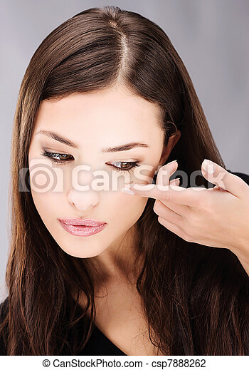 Young brunette woman holding contact lens on finger in front of her eye - csp7888262