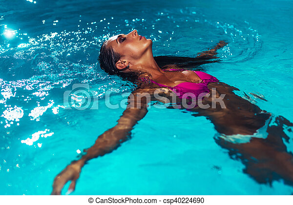 Young brunette woman relaxing in the swimming pool. - csp40224690