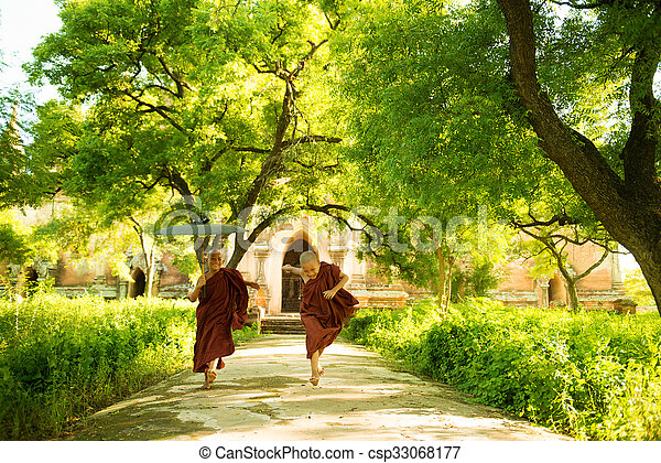 Young Buddhist novice monks running outside monastery - csp33068177
