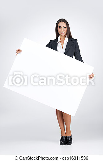 Young business woman holding big blank poster. Standing isolated on white  - csp16311536