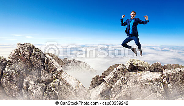 Young businessman feels success and jumps up over mountains - csp80339242