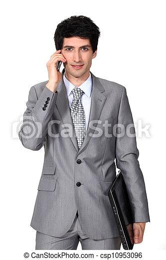 young businessman holding a briefcase and talking on his cell - csp10953096