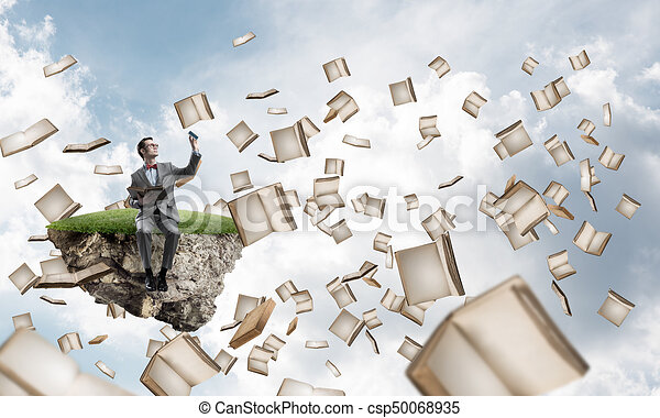 Young businessman or student studying the science and books fly around - csp50068935