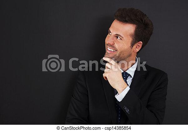 Young businessman peeking at empty blackboard   - csp14385854