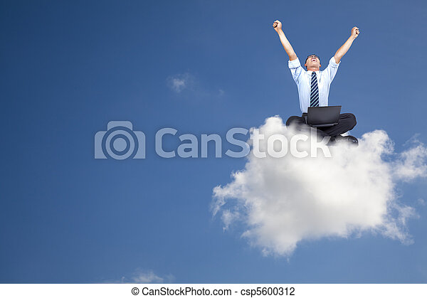 young businessman with computer sitting on the cloud - csp5600312