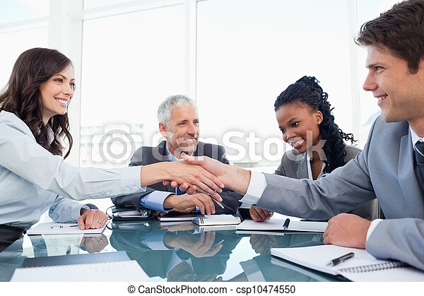 Young businesswoman and a co-worker shaking hands during a meeting - csp10474550