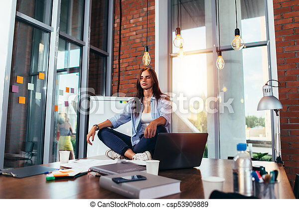 young businesswoman meditating sitting on working table in
