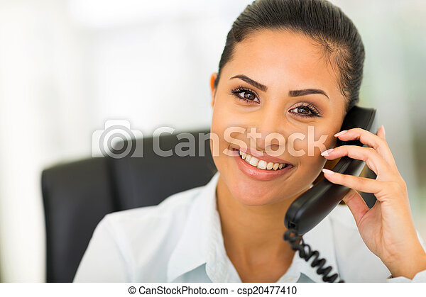 young businesswoman using landline phone - csp20477410