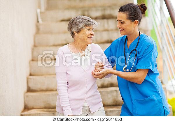 young caregiver helping senior woman - csp12611853