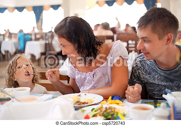 young caucasian family having dinner together. mother, father and daughter in cafe. mum feeds girl from plug  - csp5720743