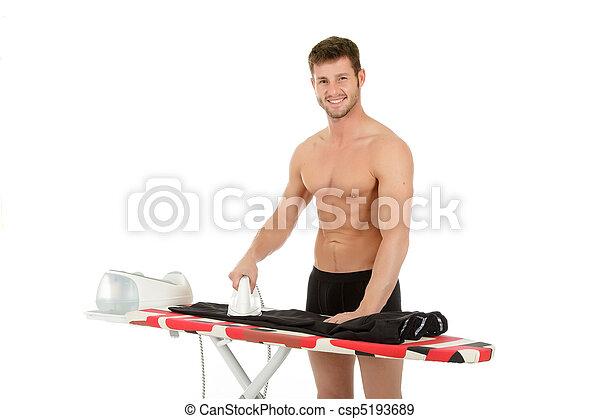Young caucasian man ironing - csp5193689