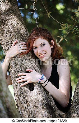 Young caucasian teen girl in tree smiling - csp4421220