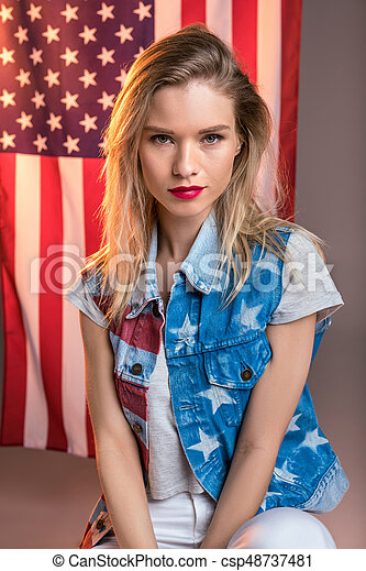 young caucasian woman looking at camera in front of USA flag, Independence Day of America - csp48737481