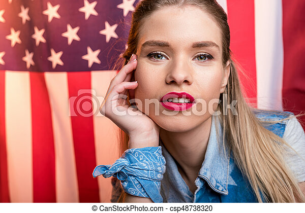 young caucasian woman looking at camera in front of USA flag, Independence Day of America - csp48738320
