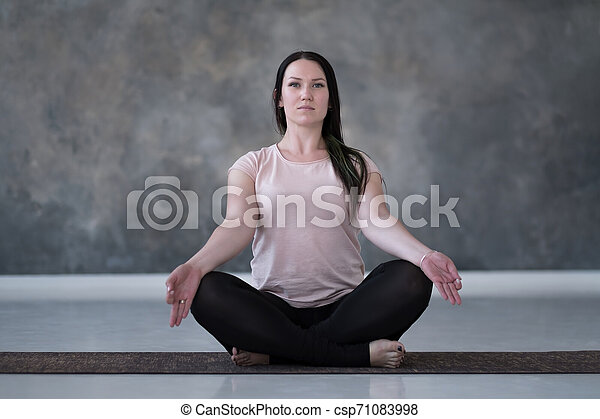 Young caucasian woman meditating on the floor - csp71083998