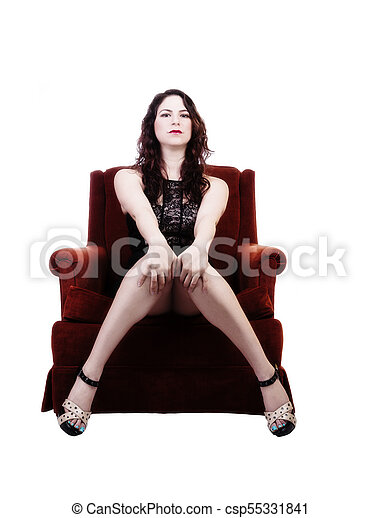 Young Caucasian Woman Sitting In Chair in Black Dress - csp55331841