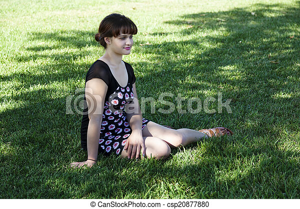 Young Caucasian Woman Sitting on Grass Shade - csp20877880