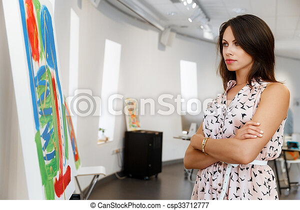 Young caucasian woman standing in art gallery front of paintings - csp33712777