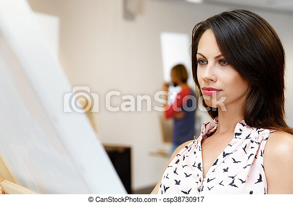 Young caucasian woman standing in art gallery front of paintings - csp38730917