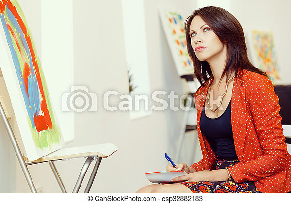 Young caucasian woman standing in art gallery front of paintings - csp32882183