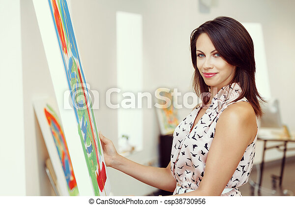Young caucasian woman standing in art gallery front of paintings - csp38730956