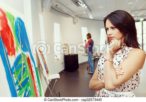 Young caucasian woman standing in art gallery front of paintings - csp32573440
