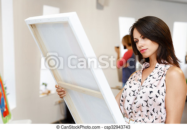 Young caucasian woman standing in art gallery front of paintings - csp32943743