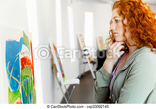 Young caucasian woman standing in art gallery front of paintings - csp33092145