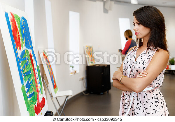 Young caucasian woman standing in art gallery front of paintings - csp33092345