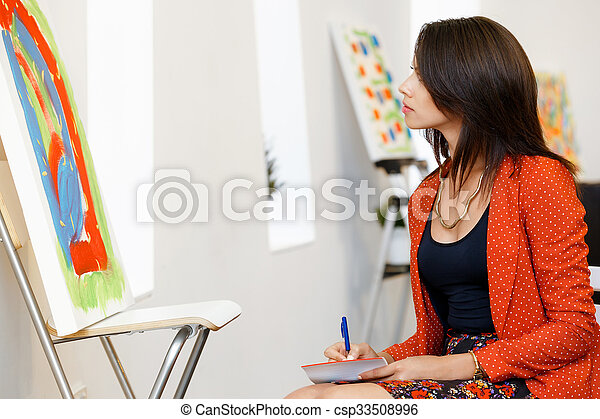 Young caucasian woman standing in art gallery front of paintings - csp33508996