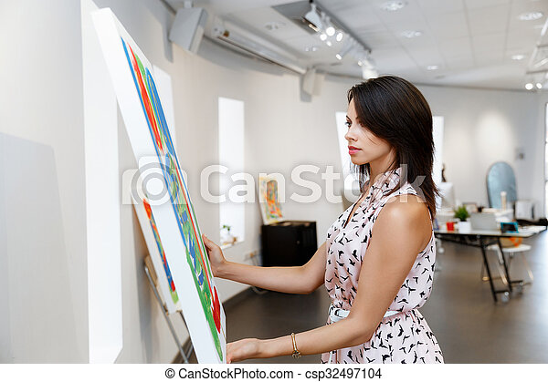 Young caucasian woman standing in art gallery front of paintings - csp32497104