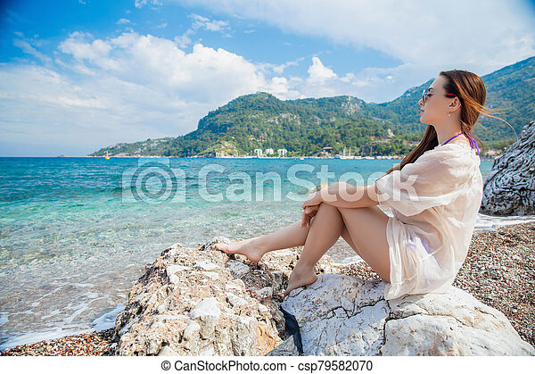 Young charming woman posing sitting - csp79582070