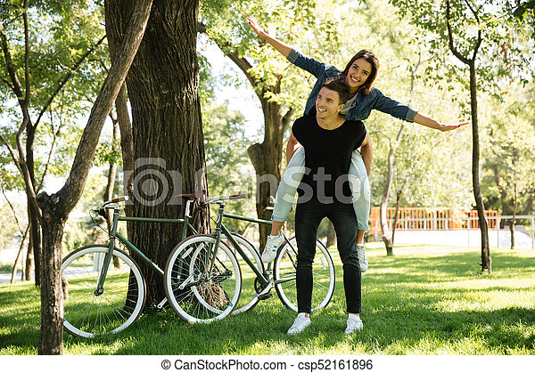 Young cheerful couple enjoying piggyback ride - csp52161896