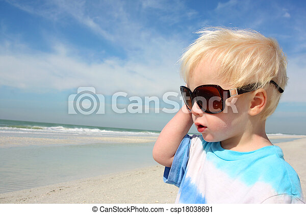 Young Child in Sunglasses Looking at the Ocean - csp18038691