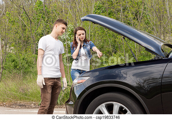 Young couple broken down at the side of a road - csp19833746