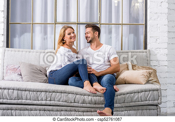 Superieur Young Couple Cuddling On The Sofa   Csp52761087