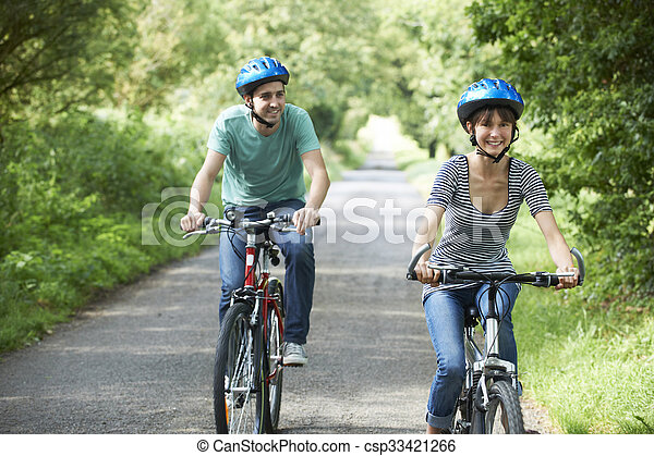 Young Couple Cycling Along Country Lane - csp33421266