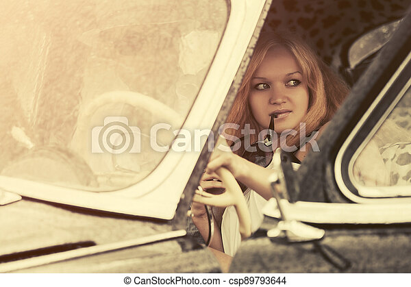 Young couple driving vintage car - csp89793644