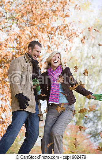 Young couple having throwing leaves in the air - csp1902479